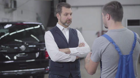 Portrait of unsatisfied adult Caucasian man talking with auto mechanic in repair Live Action