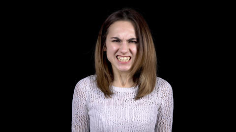 A young woman shows emotions of anger on her face. Woman screams in anger on a Live Action