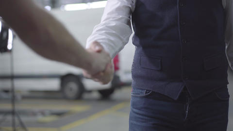 Close-up of two Caucasian men shaking hands in car repair shop. Male hands at Live Action