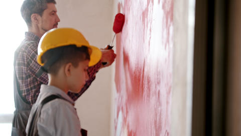 A little boy and his smiling father painting walls in red color - a boy wearing Live Action