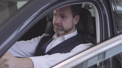 Close-up face of adult Caucasian man sitting at driver's seat and checking his Live Action