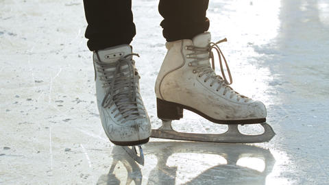 A woman standing on ice rink in figure skates Live Action