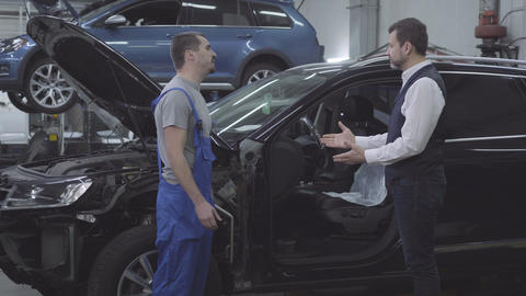 Side view of young Caucasian auto mechanic shaking client's hand in front of Live Action