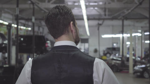 Back view of Caucasian man in vest and shirt standing in repair shop and looking Live Action