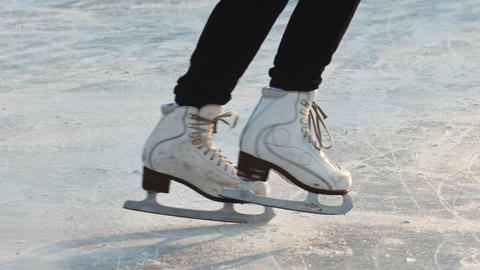 A woman skating on ice rink outdoors Live Action