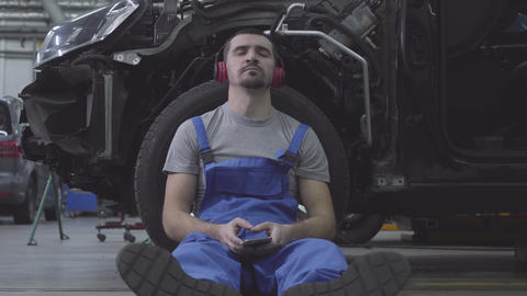 Portrait of tired Caucasian male auto mechanic leaning against car wheel and Live Action