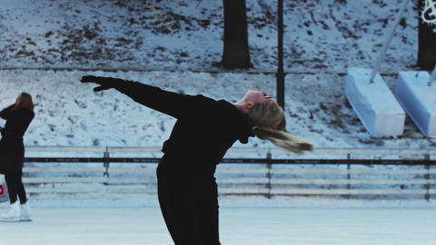 A young blonde woman figure skater spinning around herself on ice rink outdoors Live Action