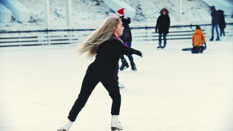 A young blonde woman professional figure skater skating on the outdoors ice rink Live Action