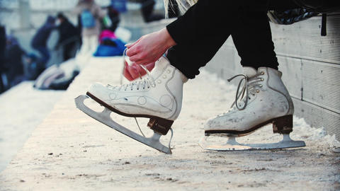 A woman tie up her figure skates Live Action