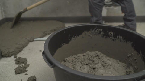 Worker puts a solution with a shovel on the floor. Worker levels the floor in Live Action