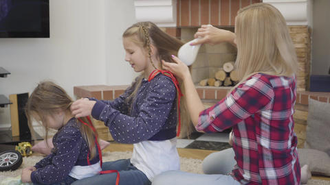 Side view of blond Caucasian woman combing elder daughter's hair as she braiding Live Action