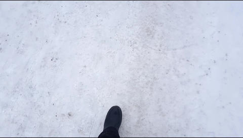 Top view, a selfie of a man walking carefully through the snow on a slippery Live Action