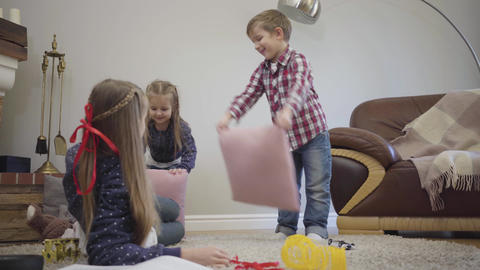 Little Caucasian boy and girl fighting elder sister with pillows, teenage girl Live Action