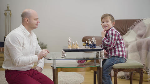 Side view of adult Caucasian man teaching little son to play chess. Little cute Live Action