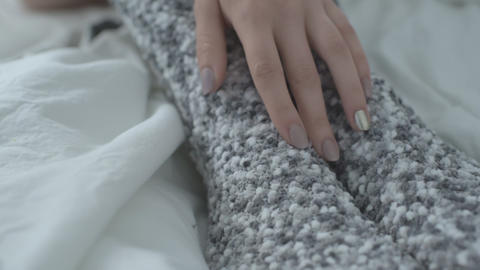 Woman in warm socks leads her hand along her leg. Close up Live Action