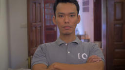 A young Asian man looks directly at the camera and huffs while he folds his arms Footage