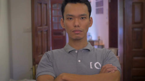 A young Asian man looks directly at the camera and huffs... Stock Video Footage