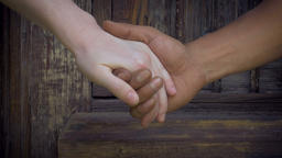 Close up of white and black hands that come together, clasp, embrace and let go  Footage