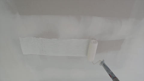 Roller painting white wall, ceiling with white paint Live Action