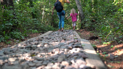 Woman with little girl walk through rough path with little stones. Foot massage Live Action