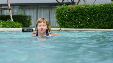 The child learns to swim in the pool Live Action
