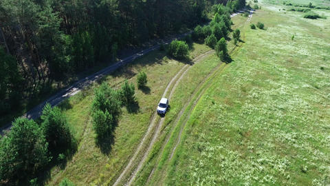 Copter view car driving through forest. Riding car going through fields Live Action
