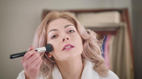 Close-up face of confident Caucasian girl applying face powder and fixing Live Action