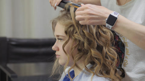 Giving the blonde hair shape and volume. Styling curls on the head of a young Live Action