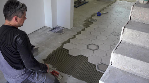 Skilled tiler apply glue and lay hexagon shape floor tiles near stairs Live Action