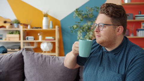 Slow motion of attractive young man drinking tea and eating cookie at home Live Action