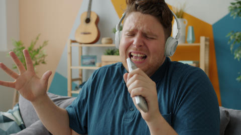 Emotional man singing in remote control wearing headphones enjoying song Live Action