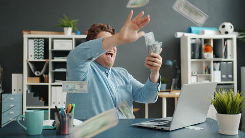 Successful businessman throwing money having fun at desk in office alone Live Action
