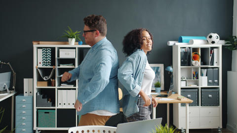 Slow motion of man and woman coworkers dancing in office, guy is falling Live Action
