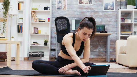 Attractive woman searching yoga exercises on tablet Live Action