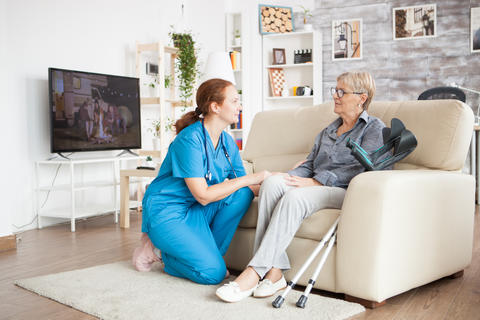 Nurse in knees talking with old woman Photo