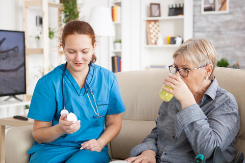 Medical nurse helping senior woman in nursing home Photo