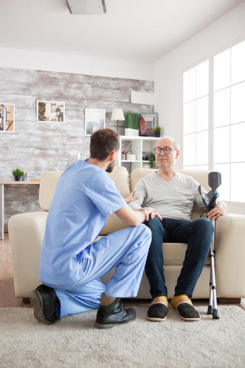Young doctor holding old man arm in nursing home Photo