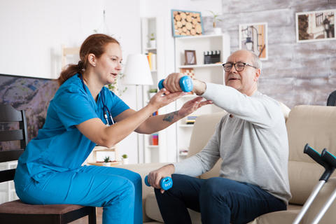 Senior man in nursing home with doing physical therapy Photo