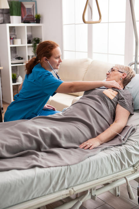 Female nurse using stethoscope to listen old woman heart Photo