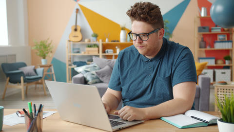 Cheerful person having fun working with laptop in apartment feeling happy Live Action