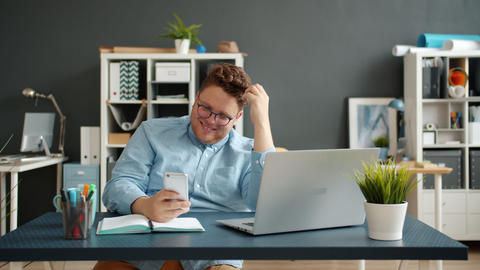 Happy guy texting using smartphone smiling working alone at desk in office Live Action