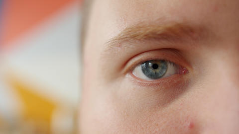 Close-up portrait of half male face eye looking at camera on colorful background Live Action