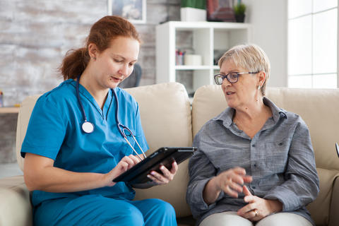 Senior woman and female nurse with tablet sitting on couch Photo
