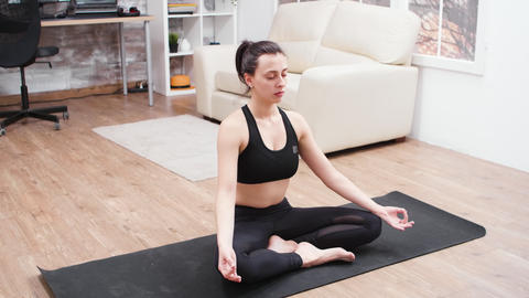 Relaxed young woman doing meditation on yoga mat GIF