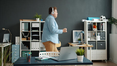 Cheerful young entrepreneur dancing in office wearing headphones relaxing with Live Action