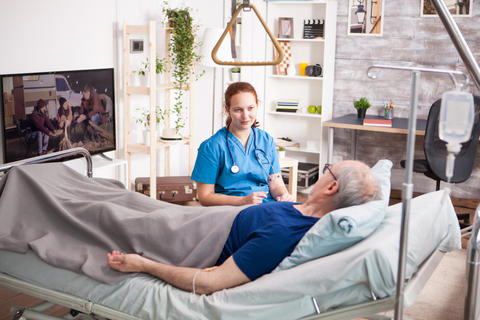 Female doctor with stethoscope sharing comfort to old man Photo