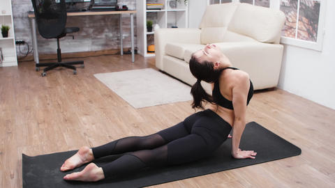 Attractive woman in leggings stretching her back GIF