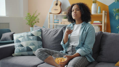 Slow motion of pretty Afro-American lady laughing watching TV eating snacks Live Action