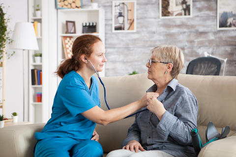 Health visitor and a senior woman in nursing home sitting on couch Photo