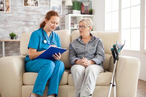 Female doctor in nursing home doing survey on senior woman Photo